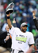 Seattle Seahawks quarterback Russell Wilson (3) holds up the NFC Championship Trophy after the Seattle Seahawks win the NFL week 20 NFC Championship football game against the Green Bay Packers on Sunday, Jan. 18, 2015 in Seattle. The Seahawks won the game 28-22 in overtime. ©Paul Anthony Spinelli