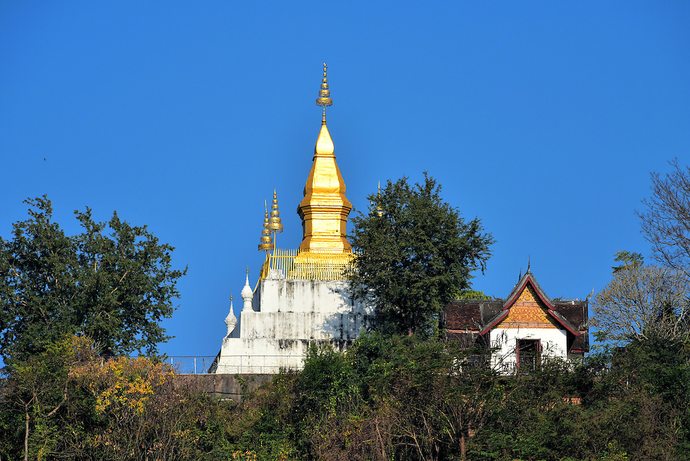 Golden Pagoda on Mount Phousi in Luang Prabang, Laos <br /> In the center of Luang Prabang is a 328 foot hill named Mount Phousi.  At the summit is this golden pagoda which shines brightly in the sun. When you stand on the white platform of Wat Chomsi, you can enjoy a panoramic view of the Nam Khan and Mekong rivers, the northern end of the Luang Prabang Mountain Range, dense forests and the city below. Watching the sunset from here is spectacular.