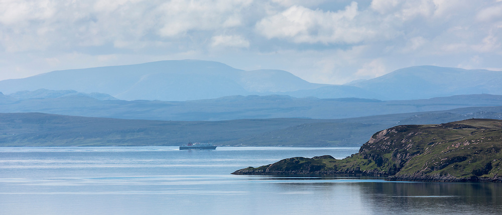 Caledonian Macbrayne ferry (Calmac) passes The Summer Isles, and in distance Isle of Skye, part of the Inner Hebrides, on route to the Outer Hebrides on the West Coast of Scotland