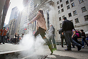 Steam leaking from the steampipes providing generator power for office buildings in New York. People are moving through the steam, as they are passing in front of the NYSE Euronext Stock Exchange on Wall Street.