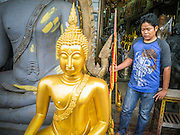 """12 NOVEMBER 2012 - BANGKOK, THAILAND:  A worker looks at a statue he helped deliver to a shop on Bamrung Muang Street in Bangkok. Thanon Bamrung Muang (Thanon is Thai for Road or Street) is Bangkok's """"Street of Many Buddhas."""" Like many ancient cities, Bangkok was once a city of artisan's neighborhoods and Bamrung Muang Road, near Bangkok's present day city hall, was once the street where all the country's Buddha statues were made. Now they made in factories on the edge of Bangkok, but Bamrung Muang Road is still where the statues are sold. Once an elephant trail, it was one of the first streets paved in Bangkok. It is the largest center of Buddhist supplies in Thailand. Not just statues but also monk's robes, candles, alms bowls, and pre-configured alms baskets are for sale along both sides of the street.    PHOTO BY JACK KURTZ"""