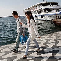 A couple walk along Kordon walkway in Izmir, Turkey