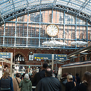 Passengers arrive on a platform under the distinctive iron and glass arched cover over the platforms of St Pancras Railway Station (now known as St Pancras International). The renovated station features distinctive Victorian architecture and serves as a Eurostar terminal for high-speed trains to Europe. There are also platforms for domestic train services. The distinctive train shed roof was designed by William Henry Barlow.