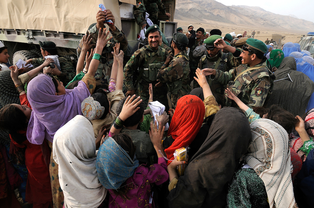"""ANA soldiers from 3rd Brigade, 201st Corps, distribute free humanitarian assistance to villagers during an operation in Tagab Valley...US Marine Colonel Jeff Haynes said the battle plan, """"The creeping barrage of goodness,"""" to win the hearts and minds of the Tagab Valley includes: a paved road, wells, radio stations, solar power, humanitarian aid, and medical outreach.  Agricultural development teaching how to package goods, and pruning techniques to increase crop yields.  Saffron cultivation started too, as a replacement to poppy.  More projects like schools and police checkpoints will follow as resources allow..."""