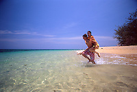 A young couple runs through the shallows of the crystal clear ocean of Low Isles, off the coast of Port Douglas in far north Queensland.