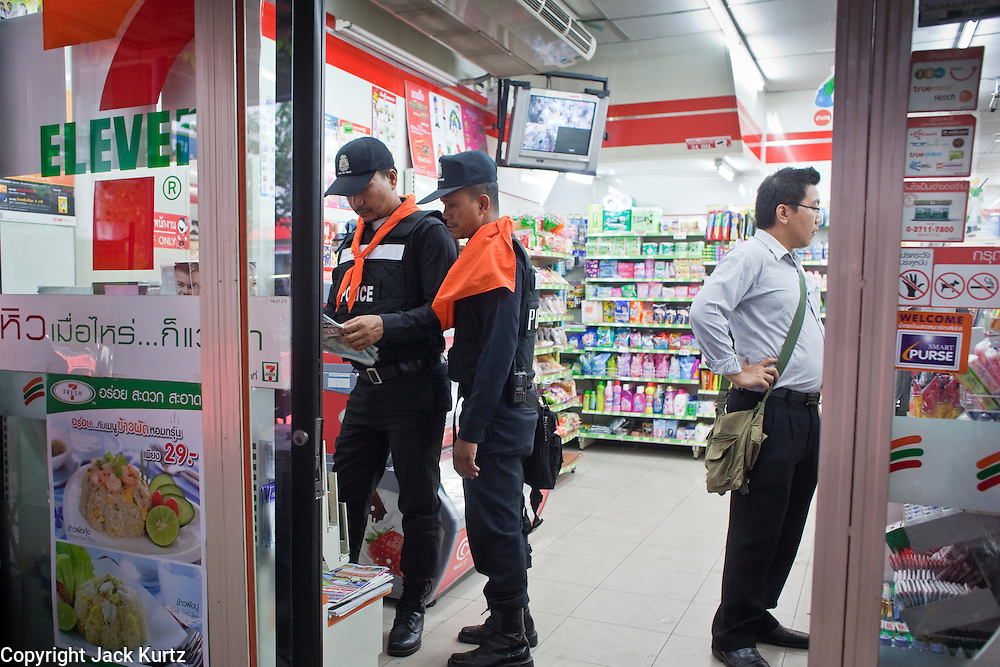 """May 12 - BANGKOK, THAILAND: Thai police shop in a 7/11 before deploying on the front line between security forces and protesters near Sala Daeng intersection. The Thai government said Wednesday that time has run out for """"Red Shirt"""" protesters in Ratchaprasong and Sala Daeng intersections in Bangkok and that a crackdown could come at any time. As news of the anticipated crackdown spread, Red Shirt protesters continued with an almost festive mood at their main stage but many of the sleeping areas around the protest site appeared to be empty. No official estimates on crowd size are available.  Photo by Jack Kurtz"""