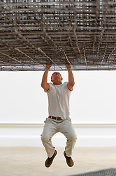 """© Licensed to London News Pictures. 16/09/2019. LONDON, UK.  Antony Gormley RA swings from his work """"Matrix III"""", 2019.  Preview of a new exhibition by Antony Gormley at the Royal Academy of Arts.  The show bring together existing and specially conceived new works from drawing to sculptures to experimental environments to be displayed in all 13 rooms of the RA's Main Galleries 21 September to 3 December 2019.  Photo credit: Stephen Chung/LNP"""