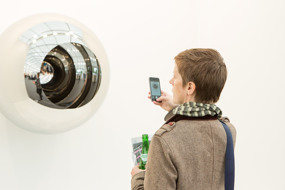 "New York, NY - 6 May 2016. Frieze New York art fair. A woman taking a photo of ""Alice - Circle"", a stanless steel sculpture by Anish Kapoor in the Lisson Gallery."