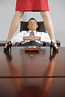 Businesswoman standing on table in front of businessman at office