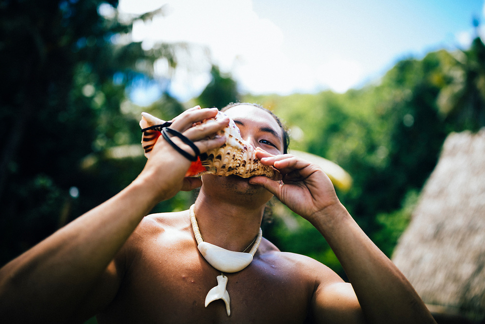 A young Chamorro man blows a conch shell to welcome visitors on Guam island.