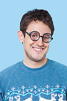 Portrait of happy young man wearing novelty glasses over blue background