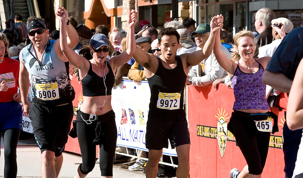 (from left)  Bryan Haakenson of Holladay, UT, no bib number, no ID, Duy Beck of Murray, UT and Chelsie Engebretson of Salt Lake City, UT cross the finish line in the half marathon at The Gateway as they competes in the Salt Lake City Marathon in Salt Lake City, Utah, Saturday, April 18, 2009. August Miller, Deseret News .