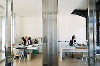 View through transparent doors of businesswoman working in office while businessman relaxes.