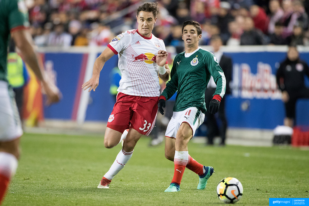 HARRISON, NEW JERSEY- APRIL 10: Isaac Brizuela #11 of C.D. Guadalajara is challenged by Aaron Long #33 of New York Red Bulls during the New York Red Bulls Vs C.D. Guadalajara CONCACAF Champions League Semi-final 2nd leg match at Red Bull Arena on April 10, 2018 in Harrison, New Jersey. (Photo by Tim Clayton/Corbis via Getty Images)