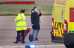 © Licensed to London News Pictures. 31/01/2020. Brize Norton, UK. A passenger films with her phone as she disembarks from a charter plane at RAF Brize Norton after being evacuated from Wuhan, China. The flight, carrying 83 Britons and 27 foreign nationals from the centre of the coronavirus outbreak, was initially delayed because of a lack of clearance by Chinese Authorities. The British passengers will travel by coach to a hospital in the north west of England for 14 days quarantine. Photo credit: Peter Macdiarmid/LNP