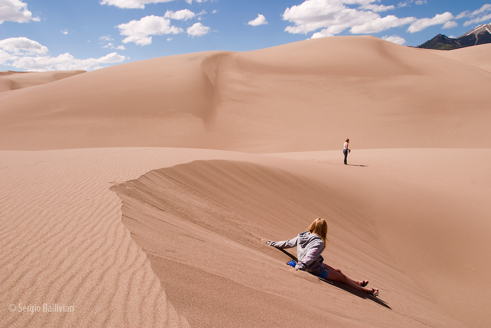 A young woman walking along a sand dune in the early afternoon at Great Sand Dunes National Park near Alamosa, Colorado
