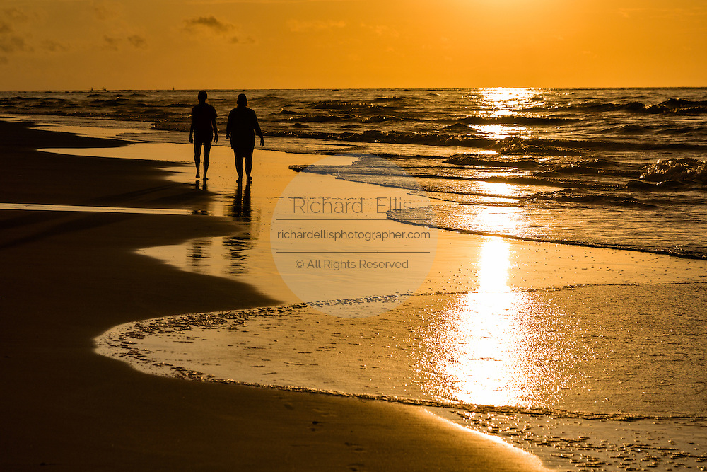 Two people silhouetted by sunrise on Isle of Palms beach at Wild Dunes near Charleston, South Carolina.