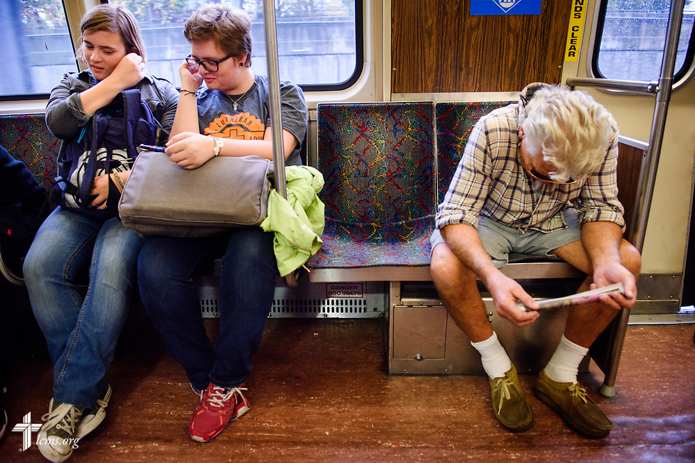 Young Adult Corps participants Rachel McCloskey and Laura Grundeman listen to music together in the subway on Wednesday, Oct. 25, 2017, in Boston. LCMS Communications/Erik M. Lunsford