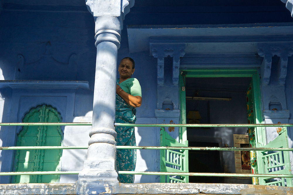"Johpur is known as ""The Blue City"" due to the Brahman neighborhoods being painted in blue.  The blue is an historic color for Brahman homes that most of the city adopted.  It is said to keep the mosquitoes at bay and the temperatures cooler.  Many of the doors are also painted green and when this women appeared wearing green she seemed just perfect for this scene."