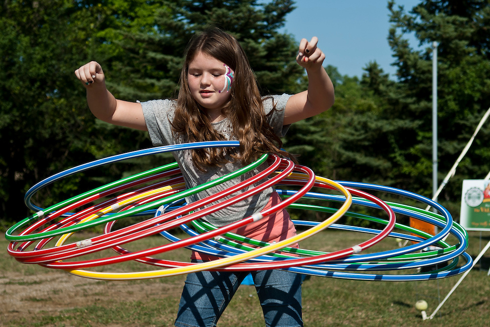 Lathan Goumas | MLive.com..Lia Norman, 11, of Flushing, attempts to use as man hula hoops as she can at the inaugural GM-UAW Summerfest in Flint, Mich. on Friday June 15, 2012.