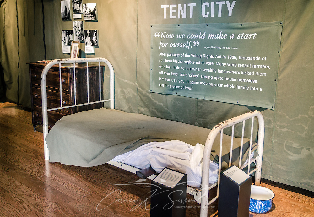 "A replica of an African-American ""Tent City"" bedroom is displayed at Lowndes Interpretive Center, Feb. 3, 2015, in Hayneville, Ala. After the passage of the 1965 Voting Rights Act, many black tenant farmers registered to vote and were kicked off their land by the weathy, white landowners. Residents of the Tent Cities routinely kept a shotgun beneath the mattress in case they needed it in the middle of the night. (Photo by Carmen K. Sisson/Cloudybright)"