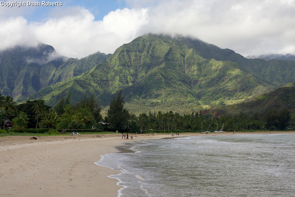 Beach at Hanalei Bay with mountain backdrop.