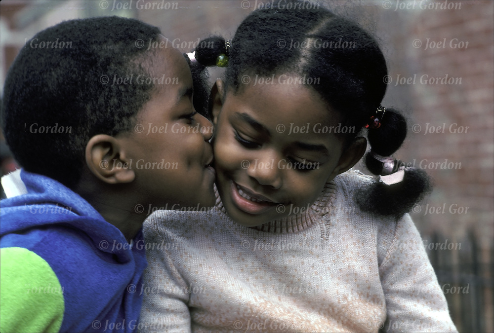 First kiss African American preadolescent boy kissing girl on cheek as she smiles back
