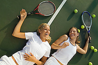 Women Fatigued and Laughing lying on tennis court After Tennis Match view from above