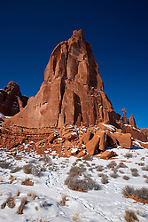 Large red sandstone rock formation with snow in winter, Arches National Park, Utah, United States of America