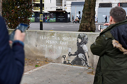 "© Licensed to London News Pictures. 27/04/2019. LONDON, UK.  People view an artwork which has appeared on a wall at Marble Arch following ten days of protests in London by Extinction Rebellion, a group demanding that governments take action to tackle climate change.  Now covered in a protective plastic cover, the artwork has been attributed to the celebrated street artist Banksy and depicts an image of a plant and a girl holding a gardening tool with the Extinction Rebellion logo on it next to the text ""From this moment despair ends and tactics begin"".  Photo credit: Stephen Chung/LNP"