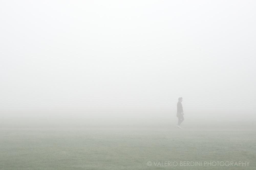 A man walking through the fog in one of the two paths crossing Parker's Piece in Cambridge, England.