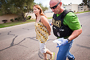 21 SEPTEMBER 2010 - PHOENIX, AZ: Detective Cory Geffre (CQ GREEN SHIRT RIGHT) escorts Donna Conner (CQ BY PHOENIX PD) to a waiting vehicle after she was arrested on drug charges in central Phoenix Tuesday. Crime has steadily dropped in Phoenix over the past few years, in line with national trends. The latest number released this month showed Phoenix reported fewer 2010 homicides, rapes, robberies, thefts - in addition to other major crimes -- compared with the same time period the previous year. Detectives in the Phoenix police department's Major Offender Unit make several arrests every day.  PHOTO BY JACK KURTZ