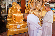 "05 JULY 2011 - BANGKOK, THAILAND:   Buddhist nuns look at Buddha statues for sale on Bamrung Muang Street in Bangkok. Thanon Bamrung Muang (Thanon is Thai for Road or Street) is Bangkok's ""Street of Many Buddhas."" Like many ancient cities, Bangkok was once a city of artisan's neighborhoods and Bamrung Muang Road, near Bangkok's present day city hall, was once the street where all the country's Buddha statues were made. Now they made in factories on the edge of Bangkok, but Bamrung Muang Road is still where the statues are sold. Once an elephant trail, it was one of the first streets paved in Bangkok, it is the largest center of Buddhist supplies in Thailand. Not just statues but also monk's robes, candles, alms bowls, and pre-configured alms baskets are for sale along both sides of the street.         PHOTO BY JACK KURTZ"
