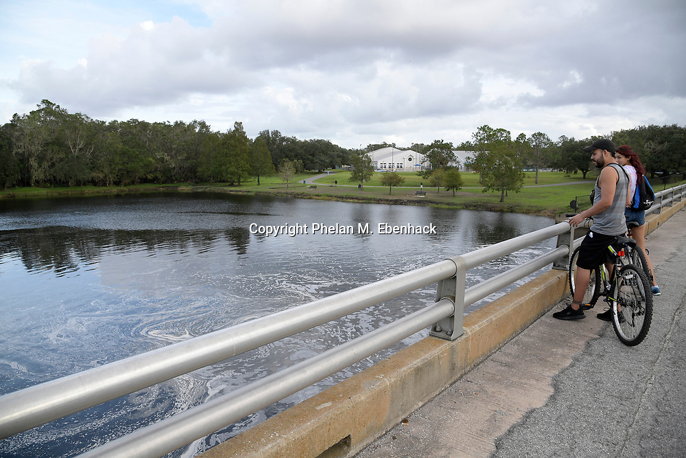 Bicyclists pause along a bridge over the Little Econlockhatchee River in Jay Blanchard Park Saturday, Oct. 21, 2017, in Orlando, Fla. (Photo by Phelan M. Ebenhack)