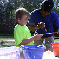 Shaw Jones, 9, gets help with his painting Saturday from Jermandy Jackson at the back to school event at Veterans park