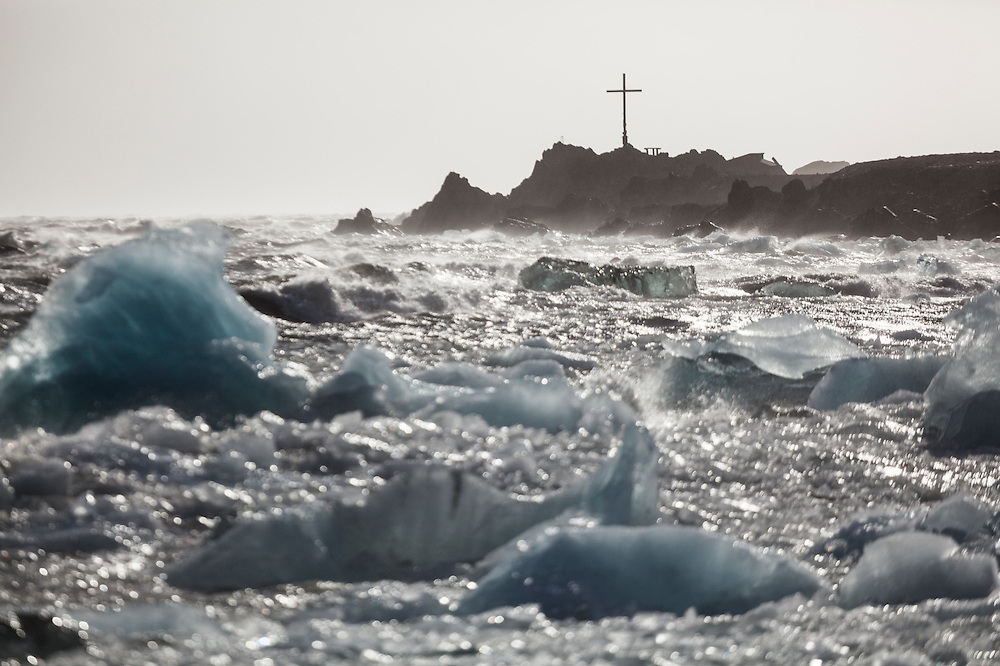 A Christian cross on the shore overlooking icebergs and rough seas outside the Polish Polar Station in Hornsund, Svalbard.
