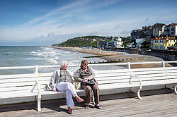 Two people enjoying the sunshine as they relax on Cromer Pier.