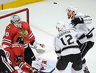 The Kings' Jeff Carter eyes the puck as it floats in front of Blackhawks' goaltender Corey Crawford during the first overtime period of Game 5 of the Western Conference Final of the 2014 NHL Stanley Cup Playoffs at United Center in Chicago Wednesday.