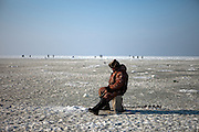 Fisherman at the ice covered port of Vladivostok in Russia, Sea of Japan (East Sea) during Ice fishing. Vladivostok, Russian Federation, Russia, RUS, 13.01.2010.