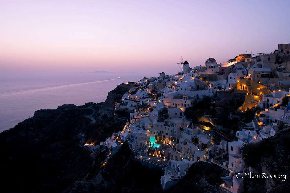 A view over Oia and the old windmill at dusk;  Santorini, The Cyclades, The Aegean, The Greek Islands, Greece, Europe