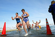 From left, Marilyn Groff, 18, and Leann Stember, 17, both of Longmont charge out of Boulder Reservoir followed by Bill Corrigan of Lakewood, during the Boulder Polar Bear Club's 24th Annual New Year's Day Ice Swim, January 1, 2007.<br /> (Longmont Daily Times-Call, )