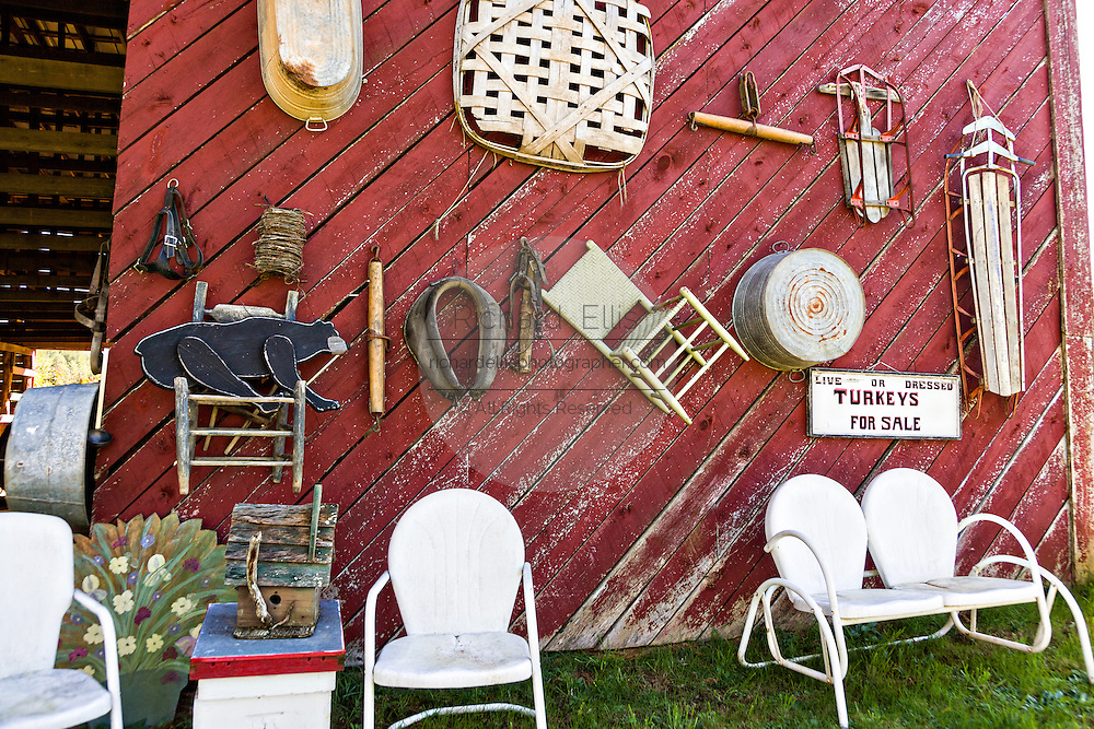 A old wooden barn decorated with an old farm implements on the Quilt Trails in Prices Creek, North Carolina. The quilt trails honor handmade quilt designs of the rural Appalachian region.