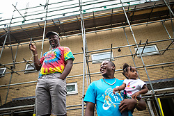 © Licensed to London News Pictures . 11/08/2018. Manchester , UK . People on Quinney Crescent watch the procession as is passes through Moss Side . The annual Moss Side Caribbean Carnival procession , celebrating dance , music and Afro-Caribbean culture , which passes in a loop from Alexandra Park and through the streets of Moss Side . Photo credit : Joel Goodman/LNP