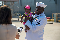 VIRGINIA BEACH, Va. (Aug. 7, 2018) Logistics Specialist 1st Class Ralph Palmer, assigned to the Harpers Ferry-class dock landing ship USS Oak Hill (LSD 51), holds his daughter during an interview after returning from deployment. Oak Hill returned to its homeport, Joint Expeditionary Base Little Creek-Fort Story, following a regularly-scheduled deployment in the U.S. 5th and U.S. 6th Fleet areas of operation. (U.S. Navy photo by Mass Communication Specialist 3rd Class Caledon Rabbipal/Released)180807-N-MW694-0159