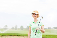 Happy middle-aged woman looking away while holding golf club