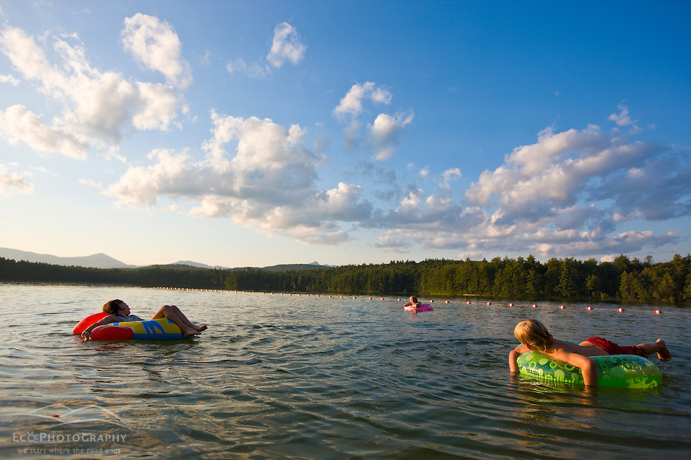 A woman and her two kids float at the beach at White Lake State Park in Tamworth, New Hampshire.
