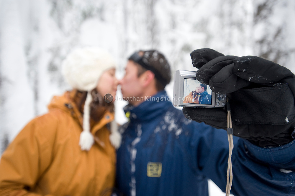 A mid adult woman and man kiss while taking a self portrait with a digital camera in a snow covered forest. (releasecode: jk_mr1035, jk_mr1034) (Model Released)