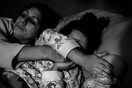 """Alejandra covers Samantha's eyes during a murder scene in the popular late-night soap opera, """"Women Assassins"""" at their home in the red-zone-sector of Belen in Merida, Venezuela. ....Alejandra says she wants Samantha to have a better life than the one she has lived, and is diligent about teaching her the importance of school, having Christian values and making good decisions. ...."""