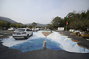 CHANGSHA, CHINA - MARCH 06: (CHINA OUT) <br /> <br />  People walk on the 3D painting on the ground of a parking lot at the Shiyan Lake on March 6, 2016 in Changsha, Hunan Province of China. The 3D painting covered an area of about 500 square meters, and showed the floating mount, rope and cliff of Shiyan Lake scenic spot in Changsha.<br /> ©Exclusivepix Media