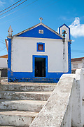 Quaint blue and white church line a street in a small town in the municipality of Obidos, Portugal